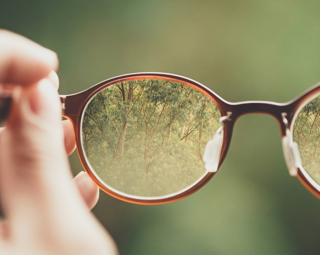 A pair of glasses against a blurry green background. Through the lens of the glasses you can see trees in a forest come into focus.