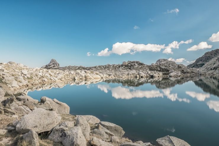 A clear lake, surrounded by rocks. On the lake is a reflection of the blue sky and white clouds.